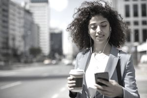 Young Woman Checks Phone With Earbuds in and Holding a Coffee While Walking Down a Downtown Street