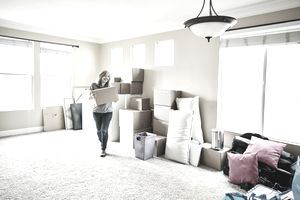 Smiling mature woman carrying box while moving into new home
