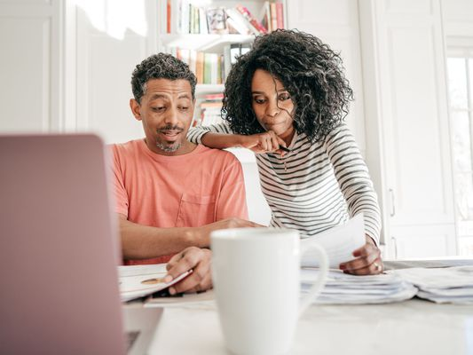African-American Man and Woman Studying Papers at a Laptop