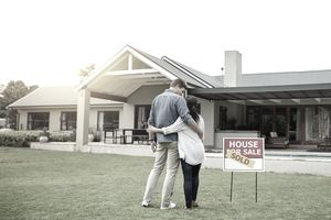 Shot of a couple standing next to a real estate sold sign at their new house