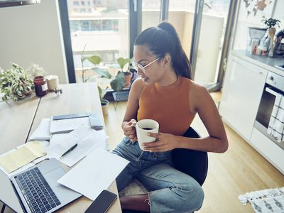 Young woman at her laptop looking over paperwork while drinking coffee
