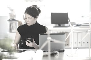 Woman using a tablet and phone in office