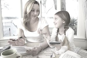 Mother sitting with daughter at table strewn with papers talking about the girl's state 529 plan