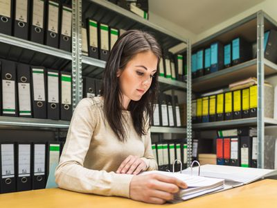 A woman looks through documents as part of a title search