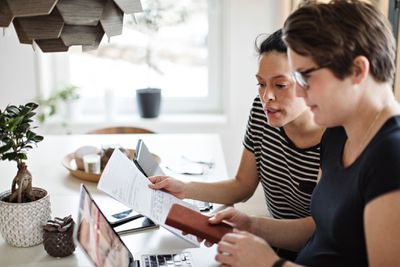 Lesbian Couple Reviewing Paperwork at a Home Table With Laptop