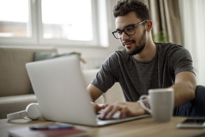 person with glasses working on computer