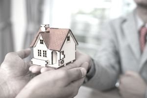 Handing a small model of a home to another person signifying buying a home