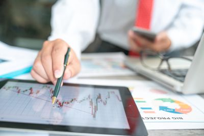 businessman using a mobile device to check stock market charts.