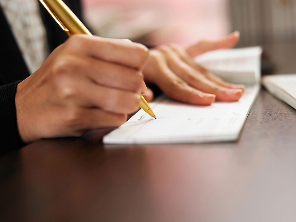 Hand of Woman Signing on Check Over Table