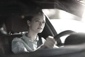 White woman driving car looking focused.