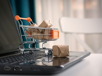 Miniature shopping cart full of packages on keyboard of a laptop