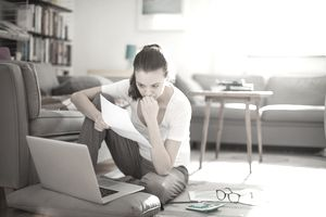 concerned woman holding paperwork and looking at laptop