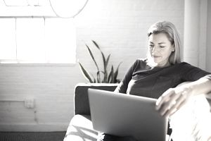 Woman With Gray Hair Looks at Laptop While Sitting on a Couch at Home.