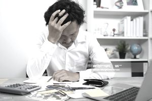 Distressed man sitting at home table with paperwork and calculator, head in his hands