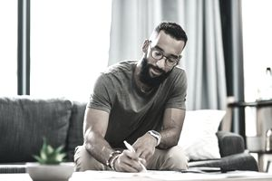 Young bearded man on sofa signs paperwork on coffee table