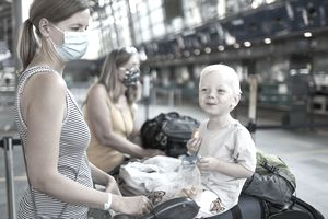A woman wearing a face mask stands with a suitcase cart piled with luggage on which her little son is sitting and eating an apple at the airport.