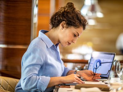 Businesswoman holding glasses looks at paper beside laptop