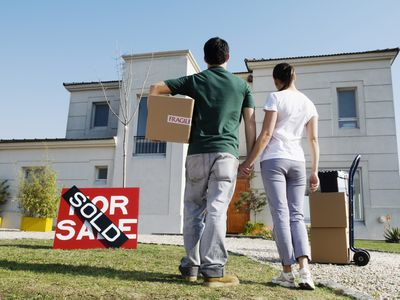 A couple in front of a home they just bought with moving boxes and a dolly sitting nearby