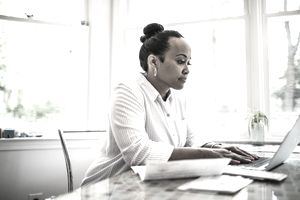 Woman in white works on a laptop in a room at home.