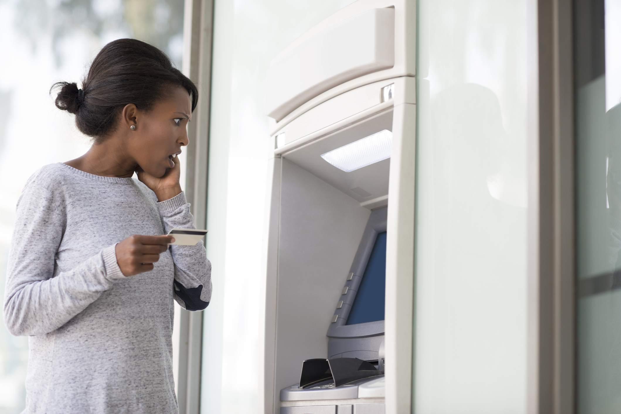 A young woman with a shocked facial expression looking at the ATM