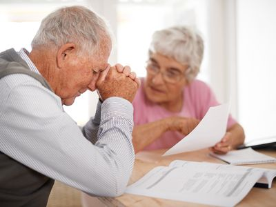Distressed retired couple looking at paperwork and frowning