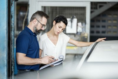Mechanic with clipboard explains charges to customer in body shop