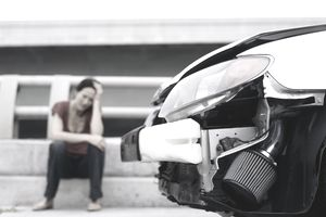 Upset woman with a suspended license sitting near her wrecked car