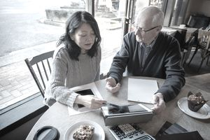 Older couple looking at finances on a digital tablet over breakfast
