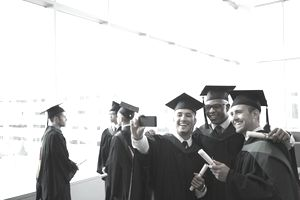 Three Young Adult Male Students in Caps and Gowns Take a Selfie Photo After Graduation