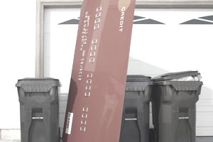 a giant credit card sits between gargabe and recycle cans in front of a grage door