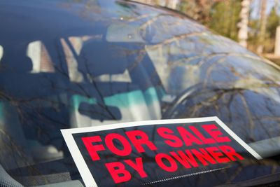 Car windshield with for sale by owner sign