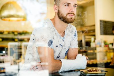 Young man with a cast on his arm sitting in a coffee shop.