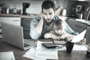 Bearded man holds daughter on his lap while he reviews paperwork and looks in a worried way at a laptop screen at home.