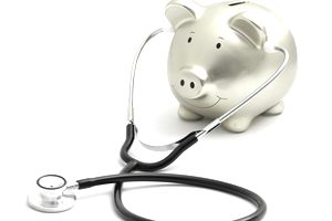 Golden piggy moneybox with a black and metal stethoscope