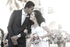 A man wearing a suit kisses a woman in bridal gown holding a bouquet at an outdoor wedding