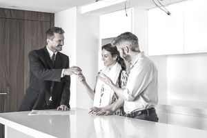 Smiling real estate agent giving house keys and documents to happy couple