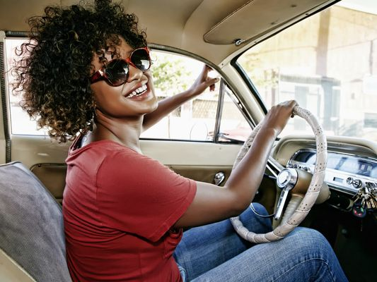 A smiling woman with natural hair and sunglasses drives her car