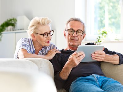 Elderly man sitting on sofa in the living room at home and showing something on digital tablet his wife.