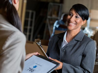 Businesswoman with a good credit score talks with a customer in a warehouse