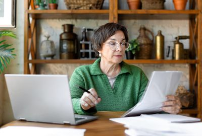 A woman sits at a desk and looks at a document to make sure it's correct