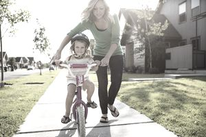Mom helping daughter ride a bike