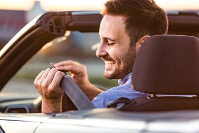 A man in the driver's seat of a convertible puts his seatbelt on