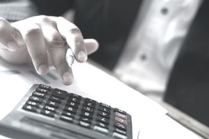 Close up business man hand using calculator for calculating cost