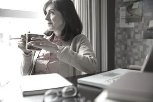 Frowning older woman sitting at a laptop with a pencil and a cup of coffee