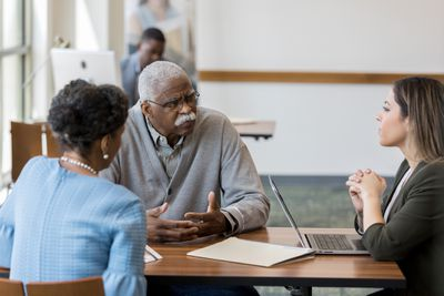 Senior couple meet with loan officer - stock photo