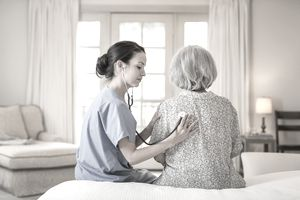 Nurse listening to woman's chest in home