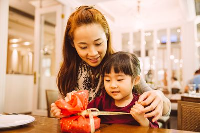 Daughter unwrapping gift with mom in restaurant