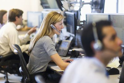 Stock traders making trades on computers and headsets