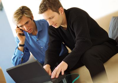 Two men look at a laptop screen while one talks on a cellphone.