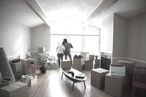 Affectionate couple at window moving into new home, surrounded by cardboard boxes